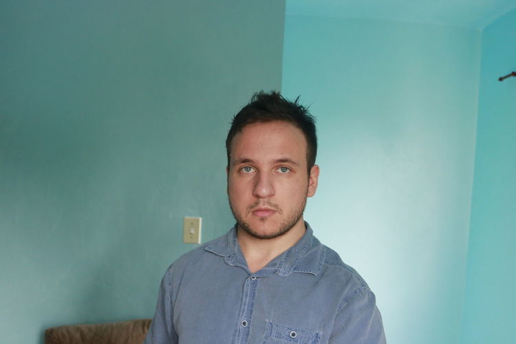 Portrait Headshot Looking At Camera One Person Real People Front View Indoors  Young Adult Young Men Casual Clothing Mid Adult Lifestyles Mid Adult Men Beard Wall - Building Feature Standing Blue Leisure Activity Contemplation Hairstyle Blue Eyes