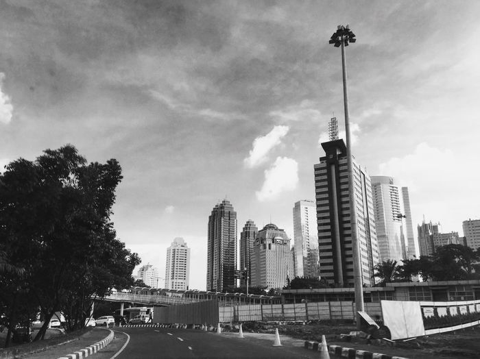 Road by buildings in city against sky