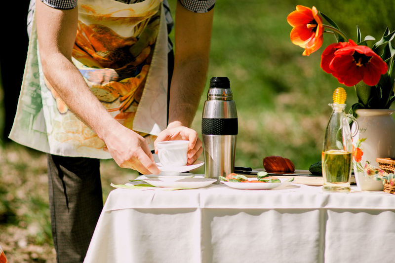Midsection of man holding cup on table
