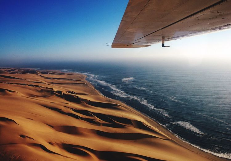Aerial view of aircraft wing over sandy beach against blue sky