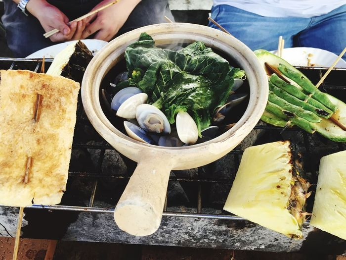 High angle view of people with food in claypot on barbeque