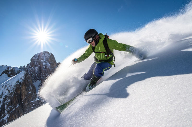 Adult man powder skiing in the backcountry of the italian dolomites.