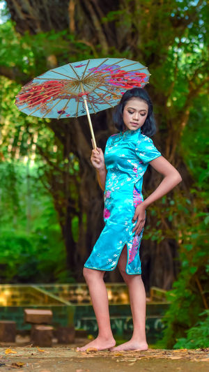 Full length of a smiling young woman standing in rain