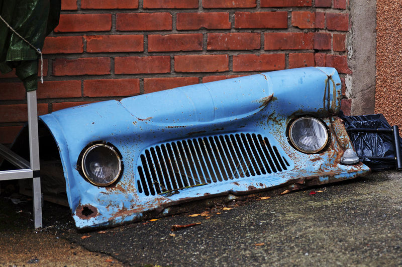 Abandoned vintage car against wall