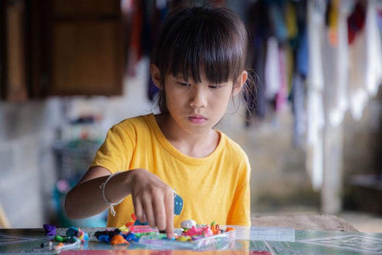 Cute girl playing with toys on table
