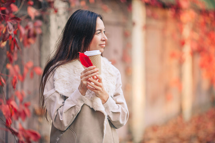 Young woman holding autumn standing outdoors