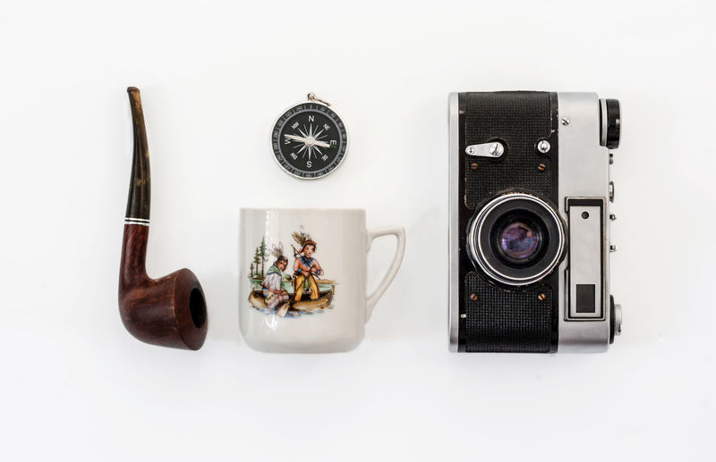 Directly above shot of camera on table against white background