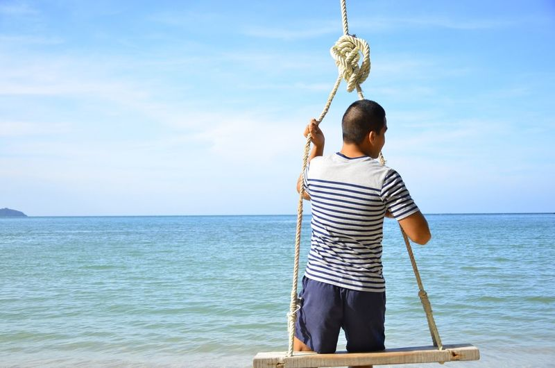 Rear view of man on swing against sea and sky