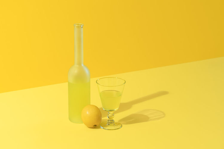 Bottle and glass of lemon liqueur limoncello on a yellow background. italian drink made with lemons
