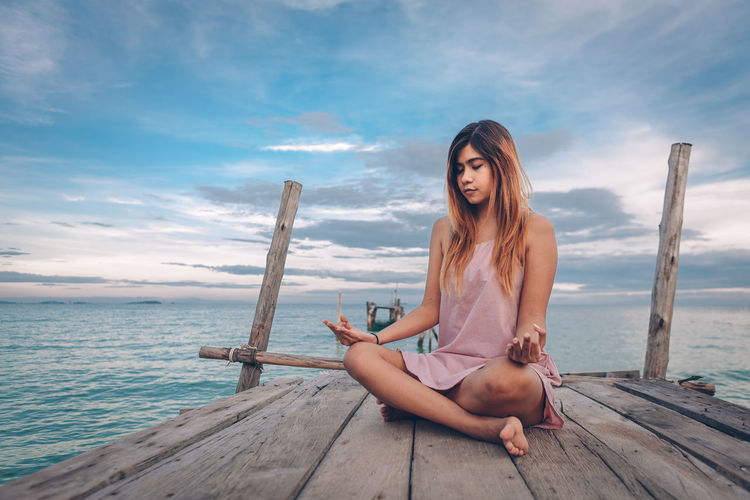 Full Length Of Woman Meditating While Sitting On Pier Against Sea And Sky