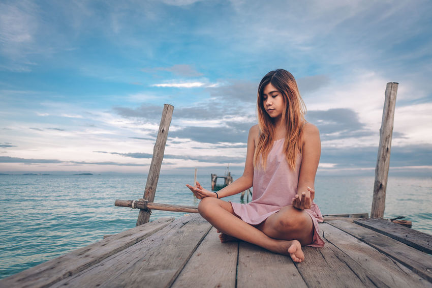 Yoka Adult Beautiful Woman Beauty In Nature Cloud - Sky Full Length Hair Hairstyle Leisure Activity Lifestyles Long Hair Nature One Person Outdoors Real People Relaxation Sea Sitting Sky Water Wood Wood - Material Young Adult Young Women