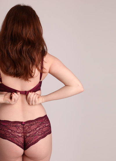 Rear view of seductive young woman wearing maroon lingerie standing against wall
