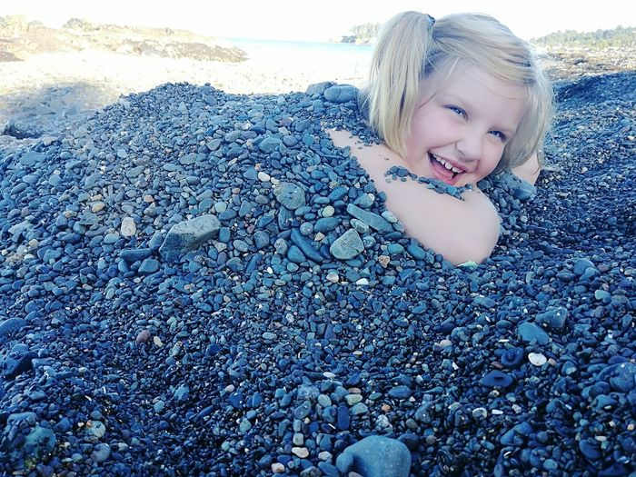 Portrait of cute girl buried in pebbles at beach