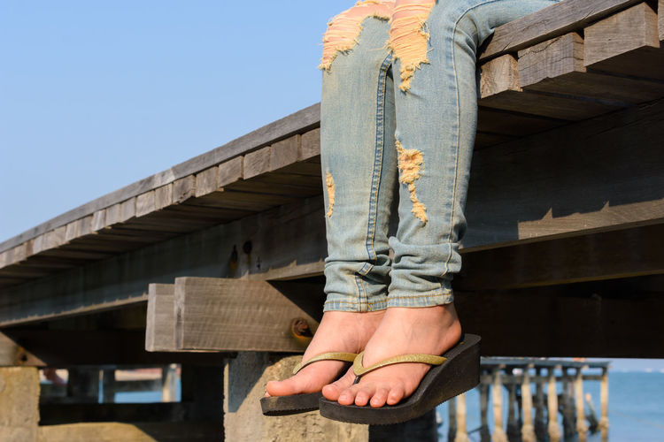 Low section of woman sitting at wooden pier