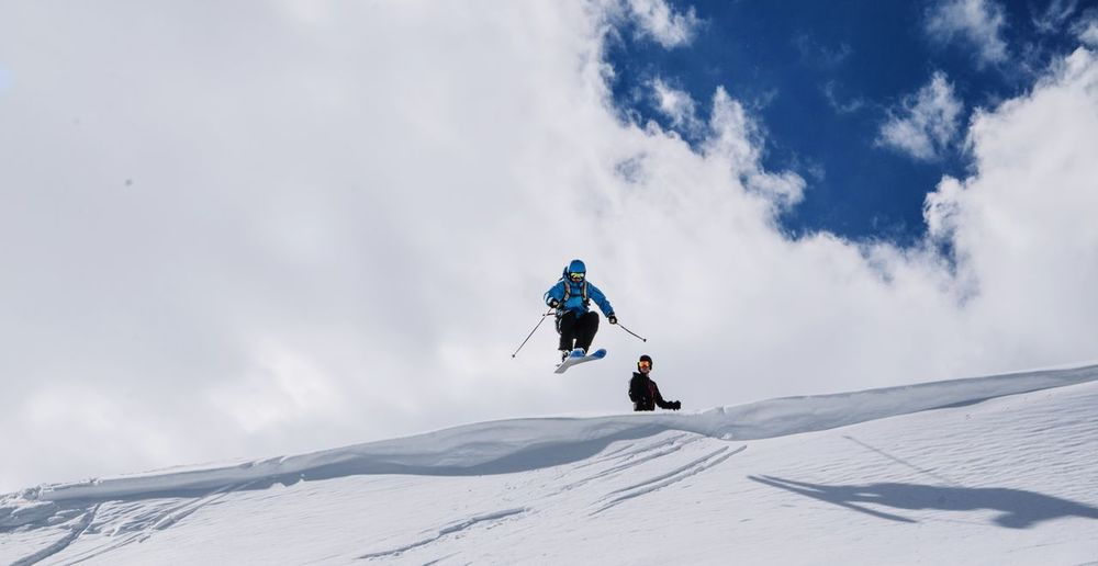 Person skiing on snowcapped mountain against cloudy sky