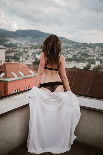 Rear View Of Woman In Bikini While Standing On Building Terrace