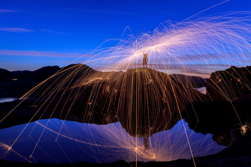 Silhouette man spinning wire wool on rock against sky at dusk