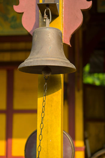 Low angle view of electric lamp hanging on yellow outside building