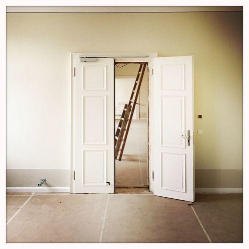 Ladder seen through ajar door at home