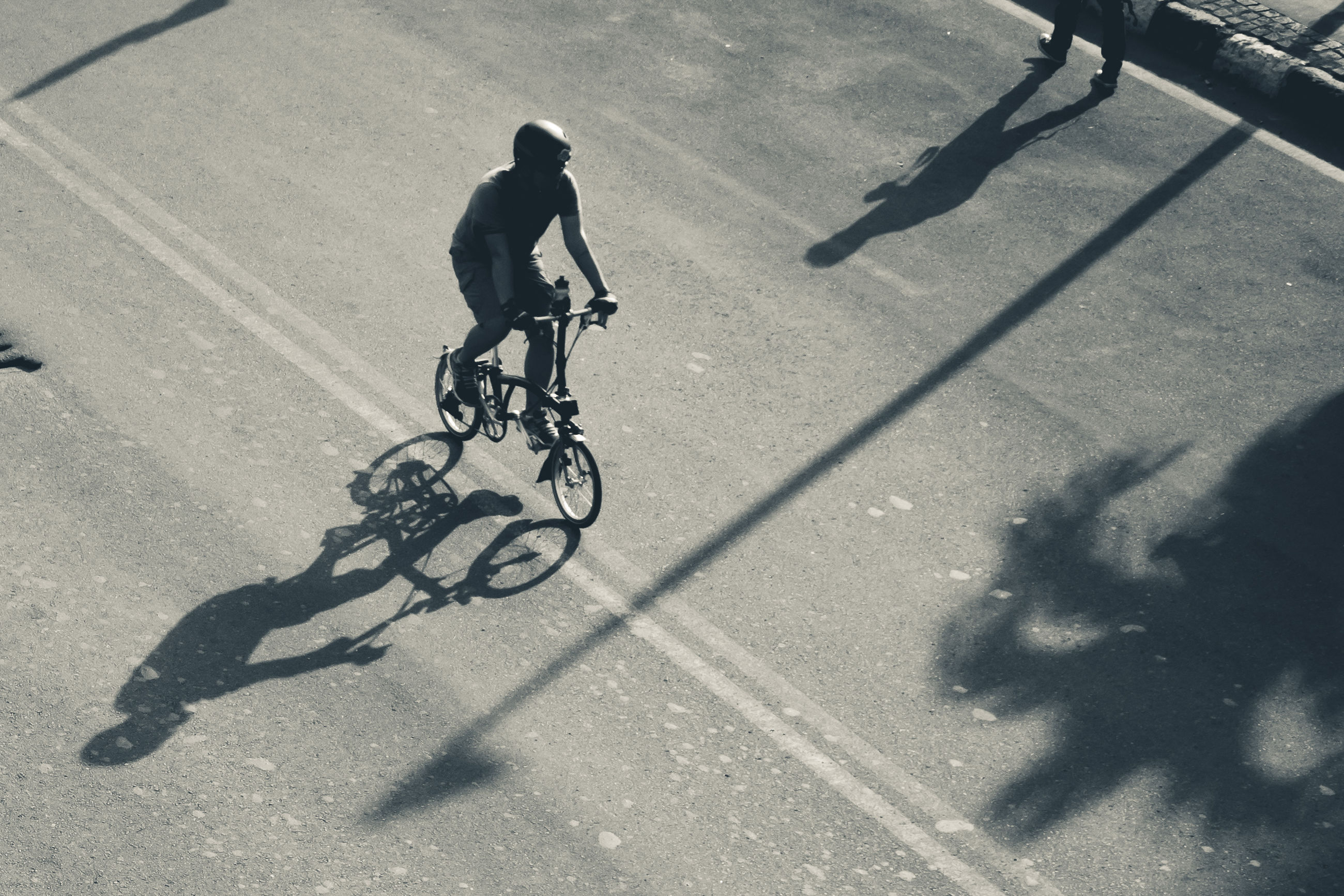 transportation, bicycle, shadow, men, sport, real people, sunlight, ride, riding, lifestyles, land vehicle, cycling, activity, city, full length, street, mode of transportation, motion, road, on the move, outdoors