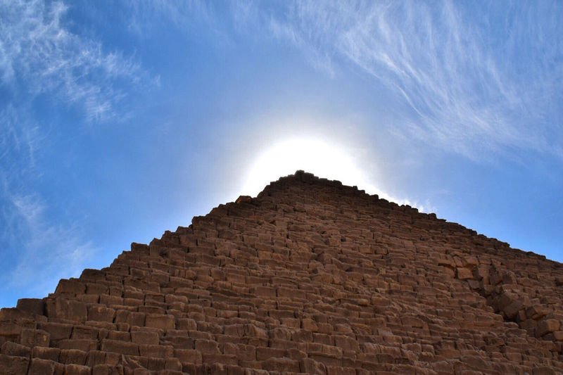 Low angle view of stone wall against cloudy sky