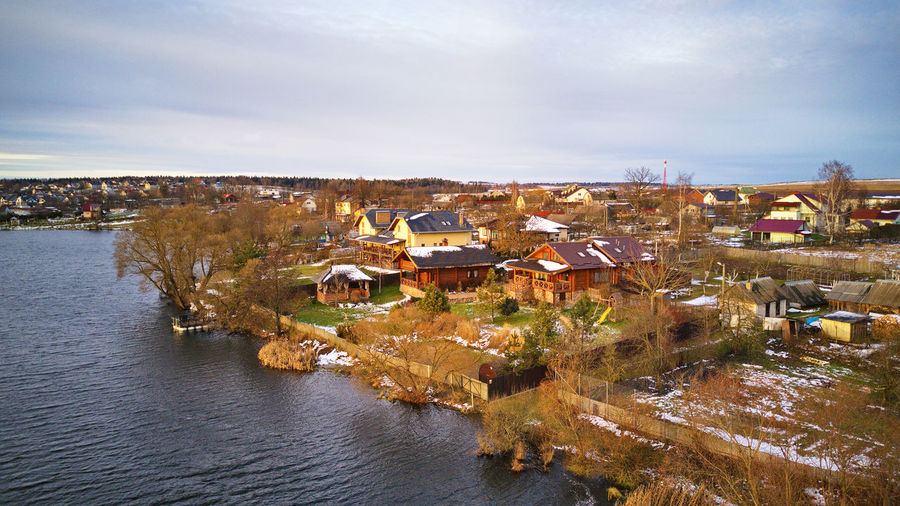 High angle view of townscape by river against sky