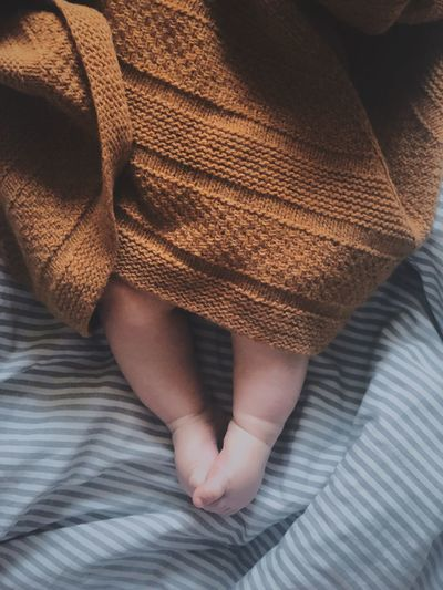 Low section of newborn baby boy wrapped in blanket on bed