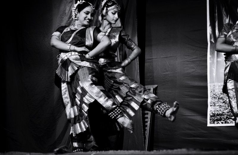 Smiling women performing traditional dance on stage