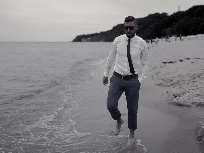 Full length portrait of young man standing on beach