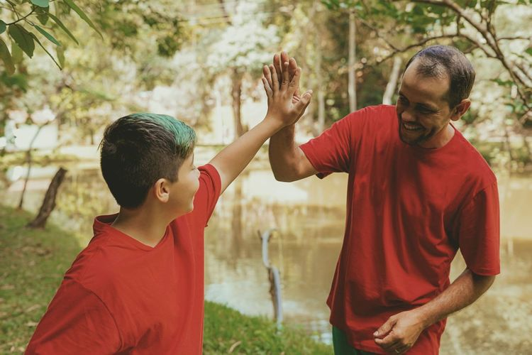 Father and son doing high-five at park
