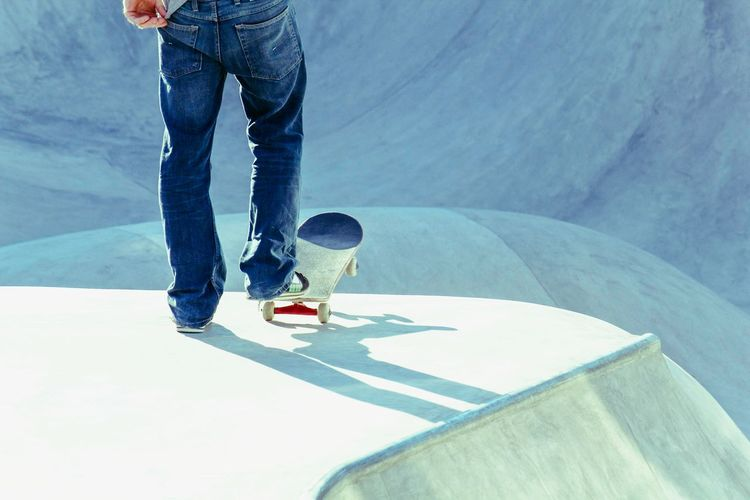 Low section of man skateboarding at skateboard park