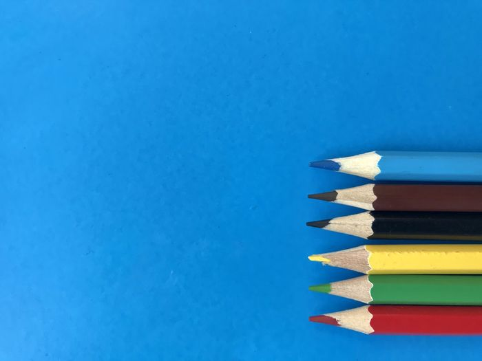 High angle view of colored pencils against blue background