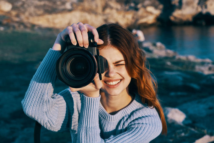 Portrait of smiling young woman holding camera