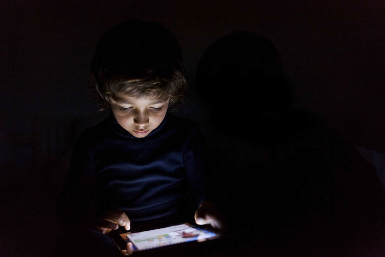 Boy looking at camera in dark room