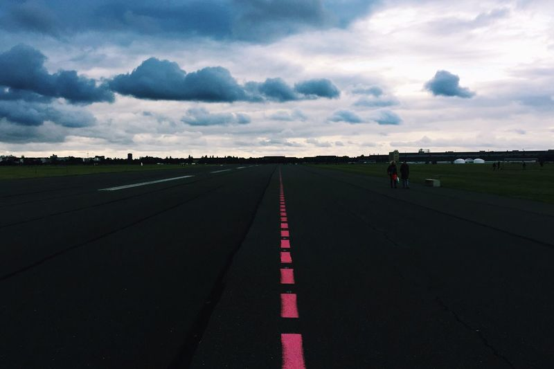 Surface level of empty road on field against cloudy sky