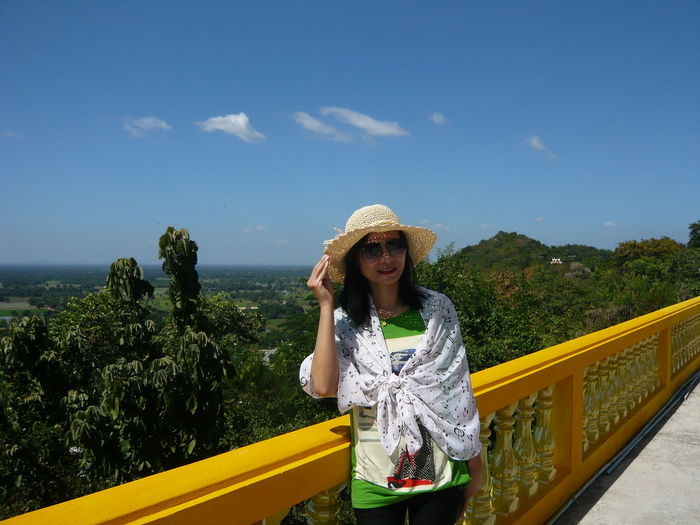 Portrait of woman wearing hat and sunglasses standing by railing against sky during sunny day