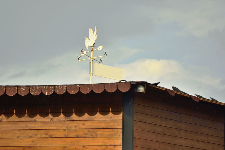 Weather Vane On Roof Against Sky