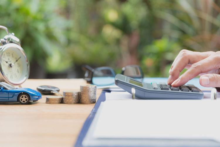 Cropped hand of businesswoman using calculator at table