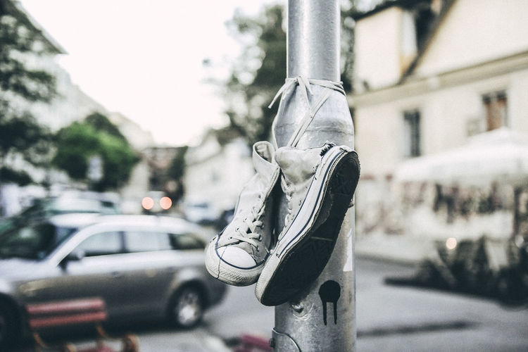 Close-up of canvas shoes tied on light pole at street