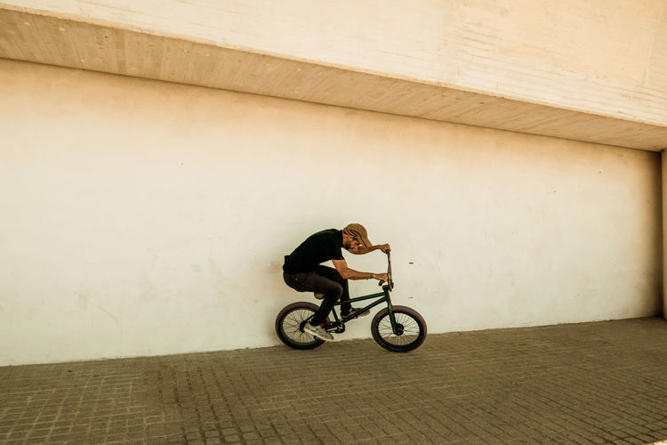 Man riding bicycle against wall