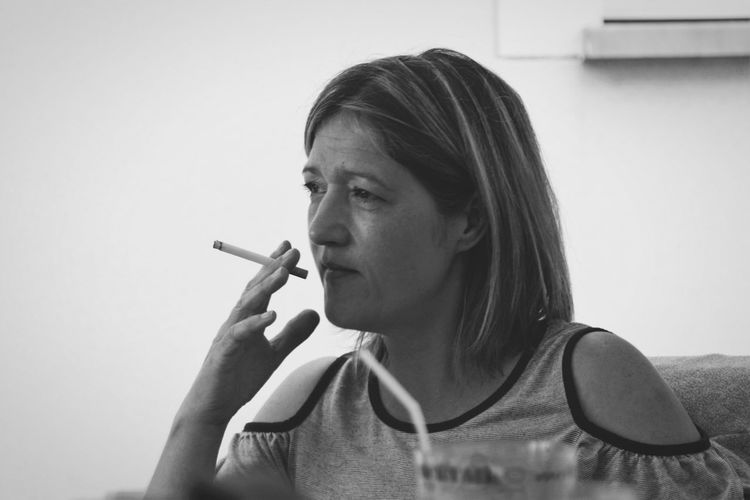 Close-Up Of Mature Woman Smoking Cigarette While Sitting On Sofa At Home