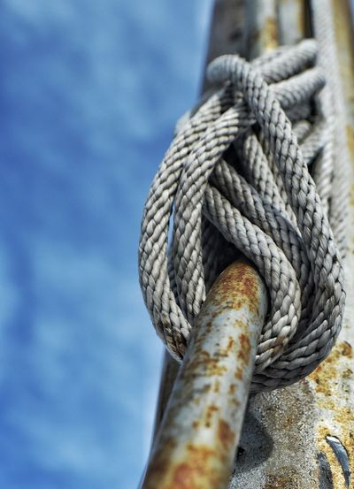 Low angle view of rope attached to rusty metal rod