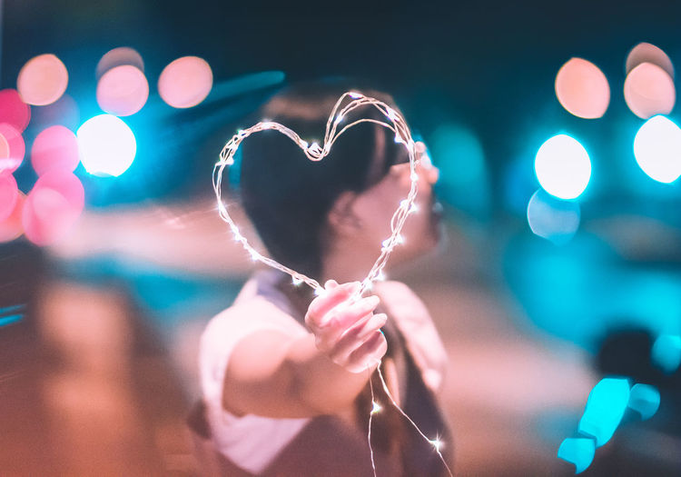 Man holding illuminated heart shape while standing on road at night