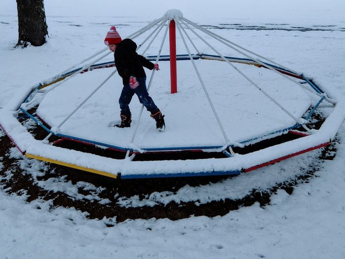 Boy playing on snow covered merry-go-round at park during winter