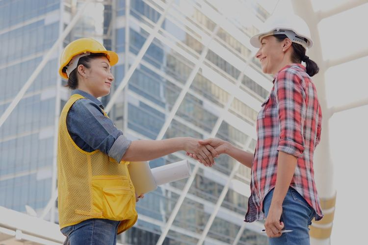 Manual workers shaking hands against building