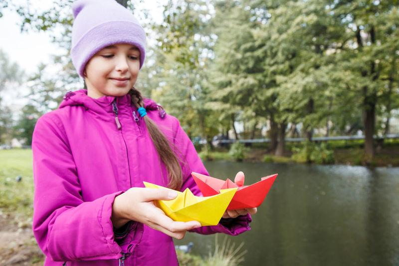 Smiling girl holding paper boat