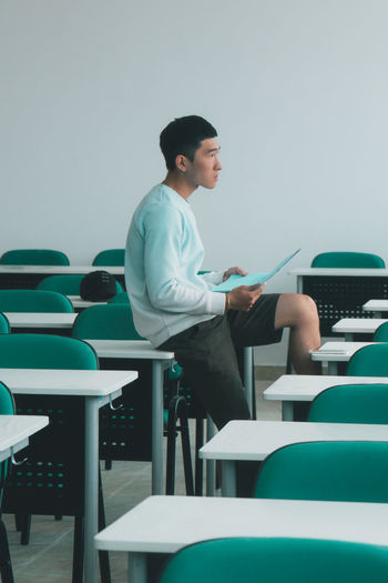 Side view of young man sitting with book on table in classroom