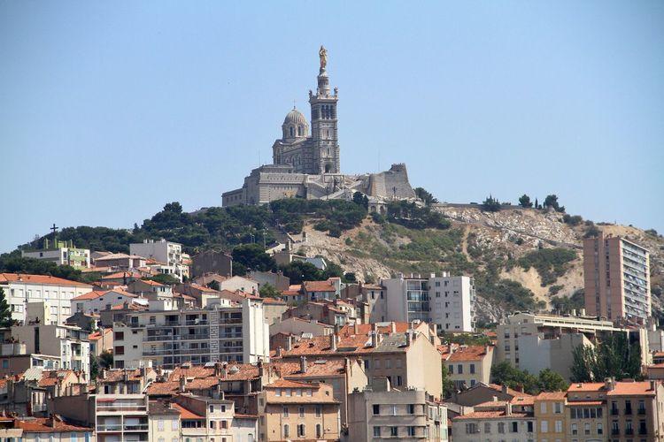 Low angle view of buildings against notre-dame de la garde