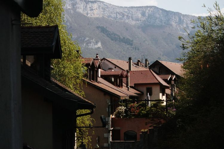 Houses in village by mountains against sky