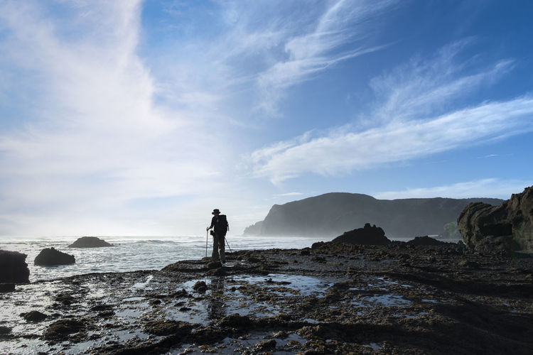 Full length of man standing on rock by sea against sky